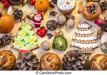 Fruits, Christmas cookies,Santa Claus,nuts,pine cones with chocolate sweets on table
