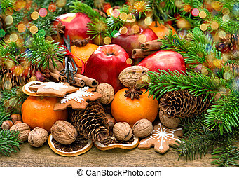 Fruits, cookies and spices. Christmas background with lights...