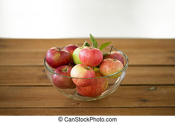 ripe apples in glass bowl on wooden table