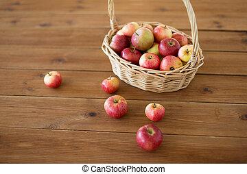 ripe apples in wicker basket on wooden table