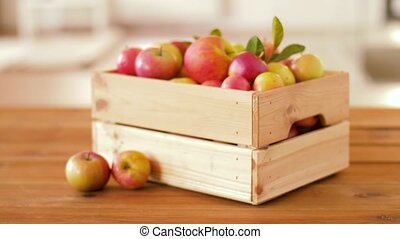 ripe apples in wooden box on table - fruits, food and...