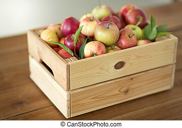 ripe apples in wooden box on table