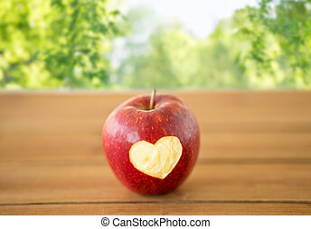 red apple with carved heart shape on wooden table