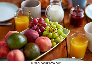 fruits, juice and other food on table at breakfast