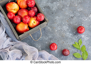 Fruits of nectarines and plums with branch with green leaves in a wooden box. Rural style
