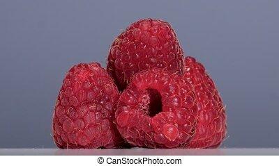 Fruits of ripe raspberry swirl on a light gray background. Close up