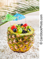 Fruits salad in pineapple with cocktail umbrellas on white pebbles