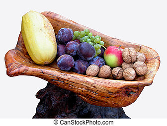 Some autumn fruits in an interesting wooden bowl.