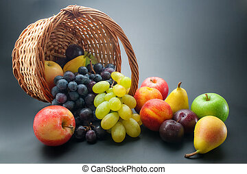 Fruits - Various fresh ripe fruits, scattered from wicker...