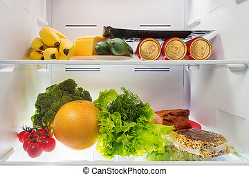 Fruits, vegetables, beer, cheese and meat into fridge