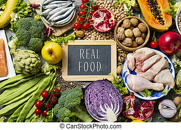 a chalkboard with the text real food written in it, on a pile of unprocessed food, such as different raw fruits and vegetables, some legumes and nuts, some pieces of chicken and some different fishes
