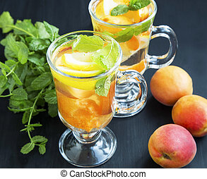 Fruits water with apricots, lemons and mint herb in glasses