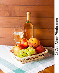 Fruits, wineglass and bottle with wine on a table