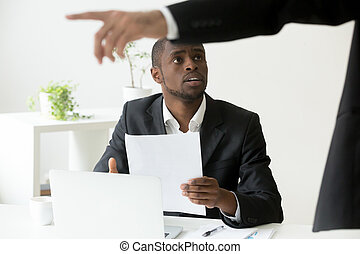 Frustrated African American worker being fired and asked to leav