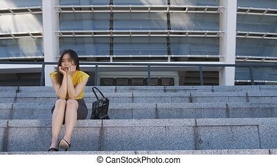Frustrated asian business woman sitting on stairs - Young...