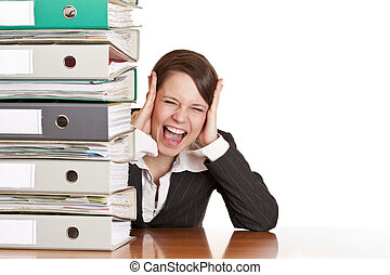 Frustrated business woman cries in office behind behind a folder stack