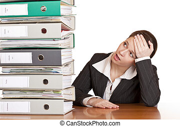 Frustrated business woman in office looks at unbelievable folder stack