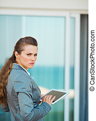 Frustrated business woman using tablet pc