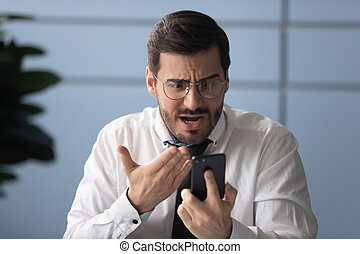Frustrated businessman angry over bad news message on smartphone.