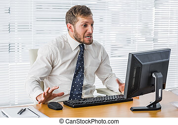 Frustrated businessman looking at his computer in his office