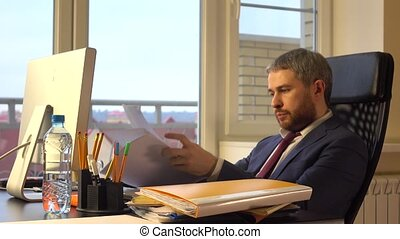Frustrated businessman torning apart the document.