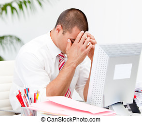 Frustrated businessman working at a computer in the office