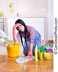 Frustrated cleaning lady - Tired young woman squatting on ...