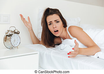 Frustrated confused woman laying in bed in the morning with...