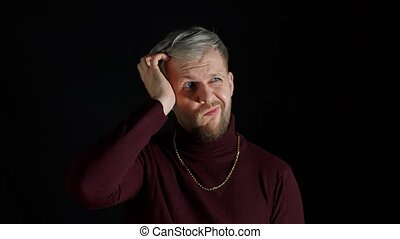 Frustrated confused young man scratching head contemplating how to solve problem, thinking intensely with puzzled look, having doubts on black background. Fashion people uncertain clueless expression