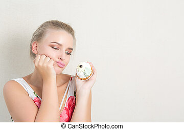 Frustrated dieting blonde lady holding delicious dessert with cream. Space for text
