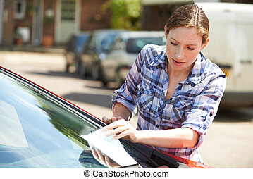 Frustrated Female Motorist Looking At Parking Ticket