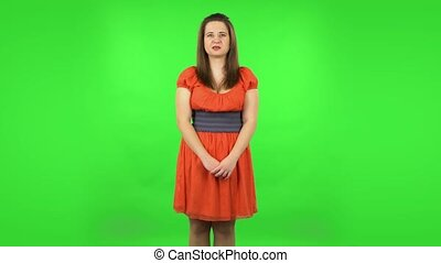 Frustrated girl saying oh my god and being shocked. Chubby girl in a coral dress with straight hair medium length and light eyes on green screen at studio