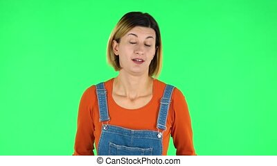 Frustrated girl says wow. Brown-eyed girl with an earring in her ear dressed an orange sweater and denim overalls on a green screen in the studio