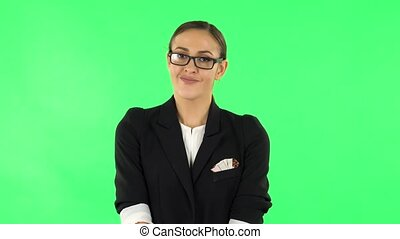 Frustrated girl says wow. Girl with dark hair and glasses wearing a black business suit at green screen at studio.