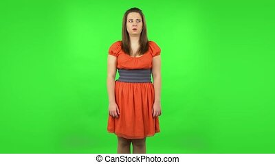 Frustrated girl says wow with shocked facial expression. Chubby girl in a coral dress with straight hair medium length and light eyes on green screen at studio