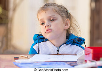 Frustrated girl sitting at a table in the yard and sad looks nowhere