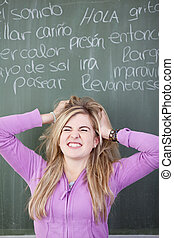 Frustrated Girl With Hands In Hair Against Chalkboard -...