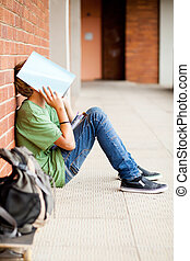 frustrated high school boy using book cover his face in...