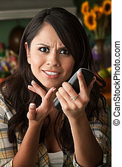 Frustrated Latina Woman on Phone Waiting for Service or...
