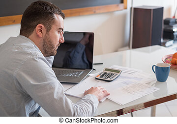 Frustrated man calculating bills and tax outcomes