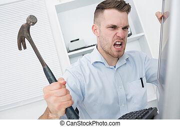 Frustrated man hitting computer monitor with hammer -...