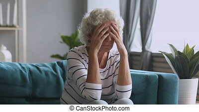 Frustrated mature woman suffering from terrible head ache at...