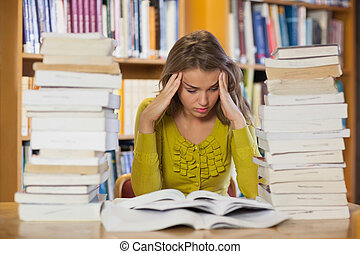 Frustrated pretty student studying between piles of books in...
