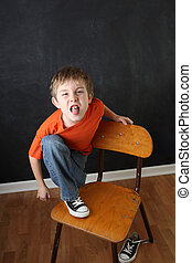 Frustrated Student - A disruptive young boy sitting on a...