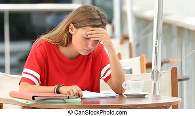 Frustrated student studying in a coffee shop - Frustrated...