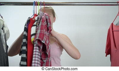 Frustrated teenage girl thinking what to dress in closet...