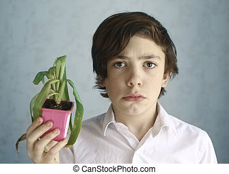 frustrated teenage kid with wilted pot plant close up ...