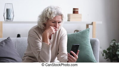 Frustrated senior lady reads bad news in mobile message concept. Sad depressed 70 years old woman looking at smart phone feels shocked. Worried elder female user customer lost money on scam fraud offer