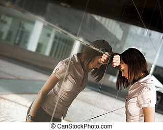 frustrated woman banging head against wall of office...