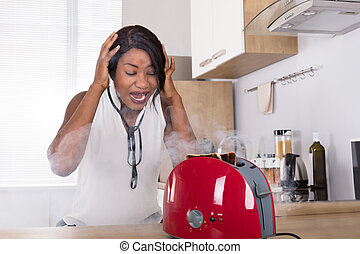 Frustrated Woman Looking At Burnt Toast Coming Out Of Toaster